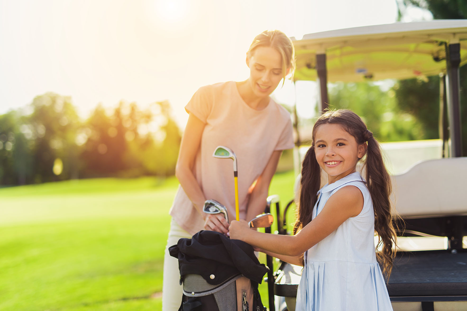 The girl takes out the golf club from the bag and looks into the lens. A woman is standing behind her and looking at the golf club she is pulling out
